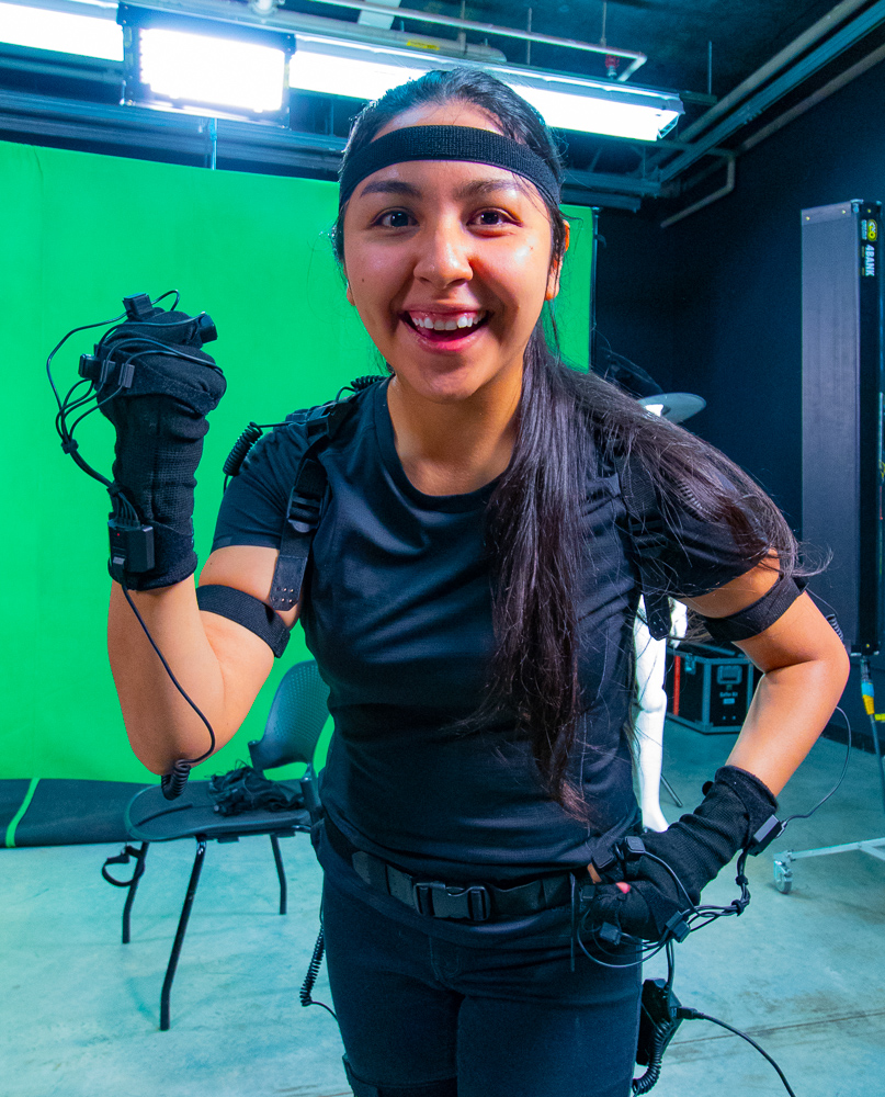 Woman wearing motion capture suit, smiling in front of green screen